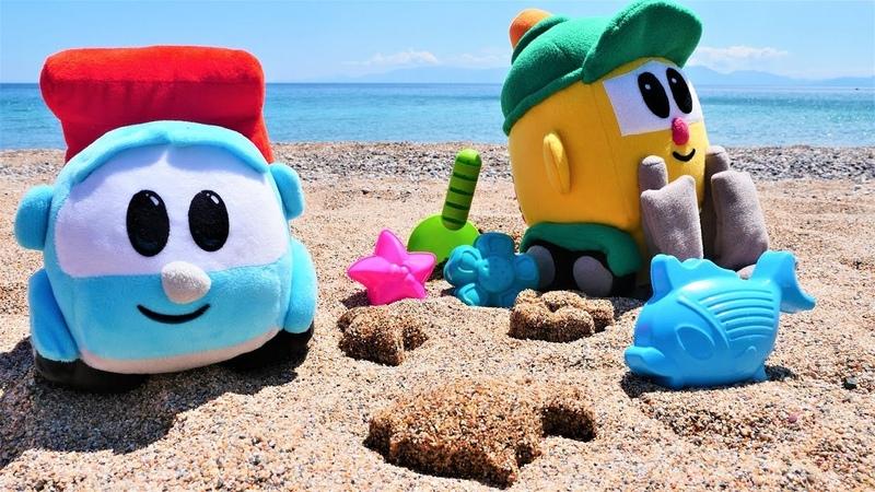 Oyuncak kamyon Leo ve Lifty plajda kum oyunlarını oynuyorlar. Plaj oyunları.