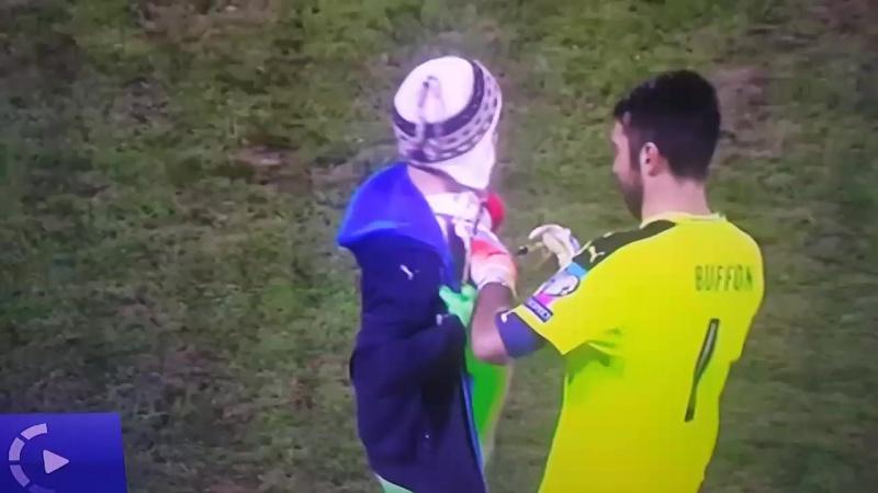 Джанлуиджи Буффон расписывается на футболке болельщика во время матча между сборными Лихтенштейна и Италии