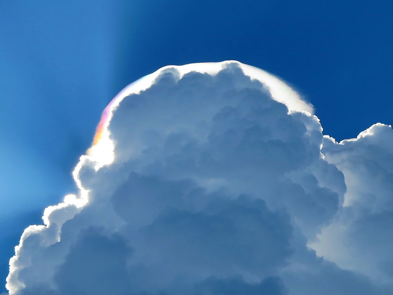Радужные облака — довольно редкое оптическое явление, при котором очень тонкие облака, находящиеся вблизи Солнца, окрашиваются в спектральные цвета. Обычно эти цвета пастельные, бледные, но при определенных условиях могут быть и очень яркими. Симпсон справедливо указал на то, что иризация является наиболее распространенным видом венцов — оптического явления, связанного с дифракцией света на каплях переохлажденной воды в облаках и образованием цветных кругов в облачной пелене вокруг Солнца. По своей сути, радужные облака — это части несостоявшихся венцов . И если полноценные венцы в атмосфере встречаются крайне редко, то радужные облака увидеть можно почти каждому, главное — быть внимательным! Наблюдать за радужными облаками лучше всего в темных очках, чтобы не ослепнуть, ведь появляются они только вблизи Солнца, на расстоянии около 3–15°, в отдельных случаях до 30°. Но если светило скрыто за чем-то (за другим облаком, за горой и т. д.), то иризацию можно увидеть и невооруженным глазом.