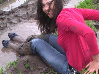 Tanya in muddy puddle and riwer fully cloused - jeans, white socks, shoes, and red t-shirt.