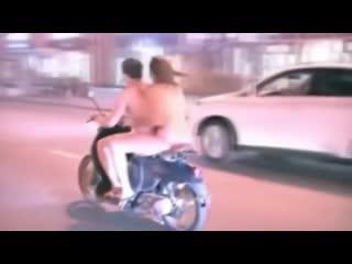 Голые девушка и парень едут на мотоцикле по улице.