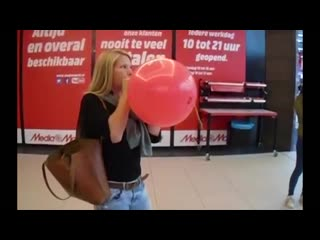 Girl blows up a red balloon and pops it by biting